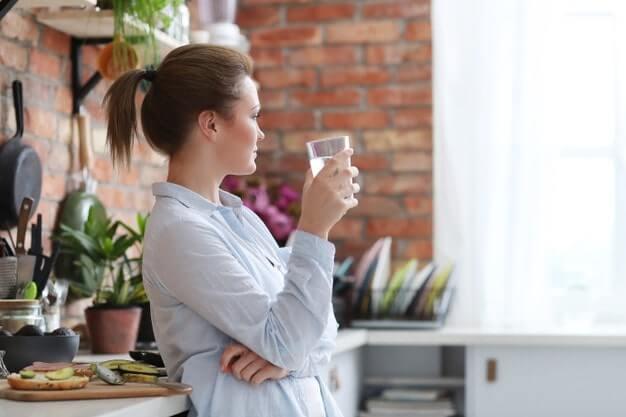femme qui boit de l'eau chez elle